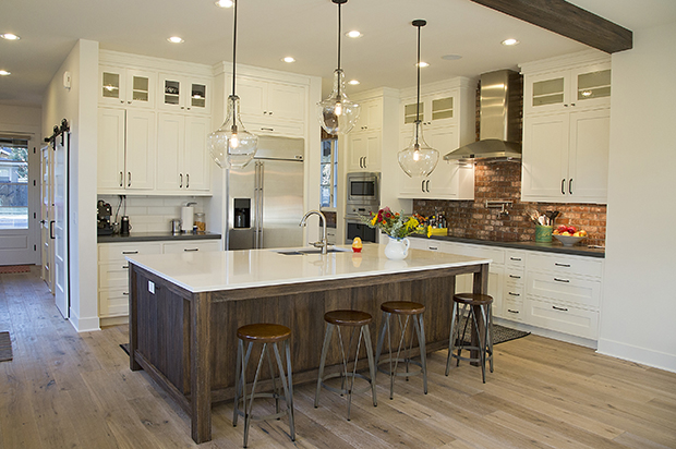 kitchen island subway tiles quartz cabinets to ceiling stainless apliances spigot over stove industrial stools beamed ceiling